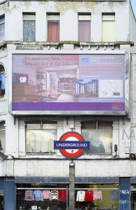 """It's surprising how at home you can feel in the city"", reads this billboard placed in a visibly run-down area of  London, above the iconic sign of a tube station (Aldgate East in Whitechapel High Street), at the boundary with the City. The ad was commissioned by Berkeley Homes and displayed by Primesight. A clothing store is visible at the ground floor of the building. Overall, the image focuses on the contrast between the rich shown in the billboard and the poor shown by real London."