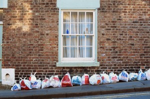 Durham, England - May 2, 2012: Most British supermarket chains (Pooundland, Tesco, Iceland, Wilkinson) are portrayed by these shopping bags used to wrap garbage and left out on the street (Allergate) for collection. A small collection of glass bottles is displayed at the window.
