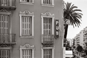 The typical urban residential architecture of the South of France (Nice) mixes with entertainment venues (a pub sign)