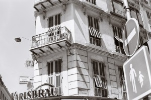 The area around the train station is full of hotels. Rue de Belgique is no exception. The signs of the hotel Capri and a Karlsbrau bar are readable. The sunny day shows the typical architecture of the area