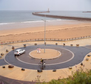 Sunderland, England - August 5, 2012: After a storm, the light conditions change the normal colour saturation of the scene: the sand appears almost as pink as the dress of one of the ladies in the centre of the roundabout. A car and a cyclist (with the usual ugly but useful yellow high-visibility vest) also arrive onto the scene immediately after the rain clears. The Roker pier is visible in the background. Scan from 120 Portra 400