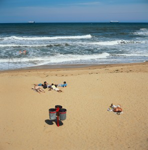 Tynemouth, England - June 26, 2011: this notoriously cold beach in Tyneside does not attract too many sunbathers. On this rare sunny day a few people attempt the outdoors and share the view with two commercial ships in the distance. Focus is on the foreground.