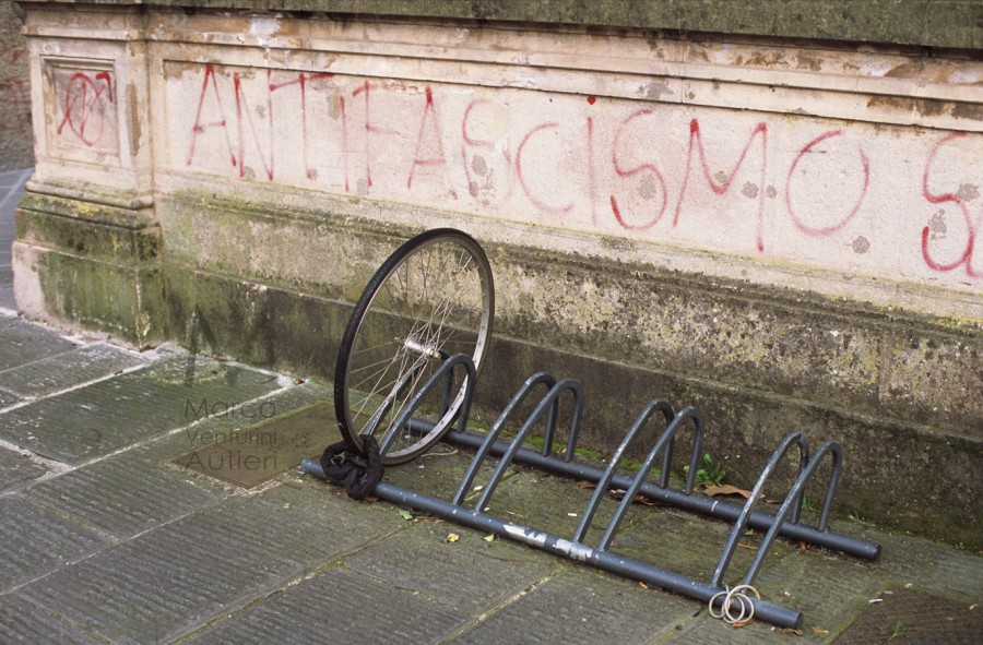 "Graffiti on a wall pro ""Antifascismo"" (Antifascism). One bicycle was stolen - only the chained front wheel is visible Piazza Dante Spring 2013"