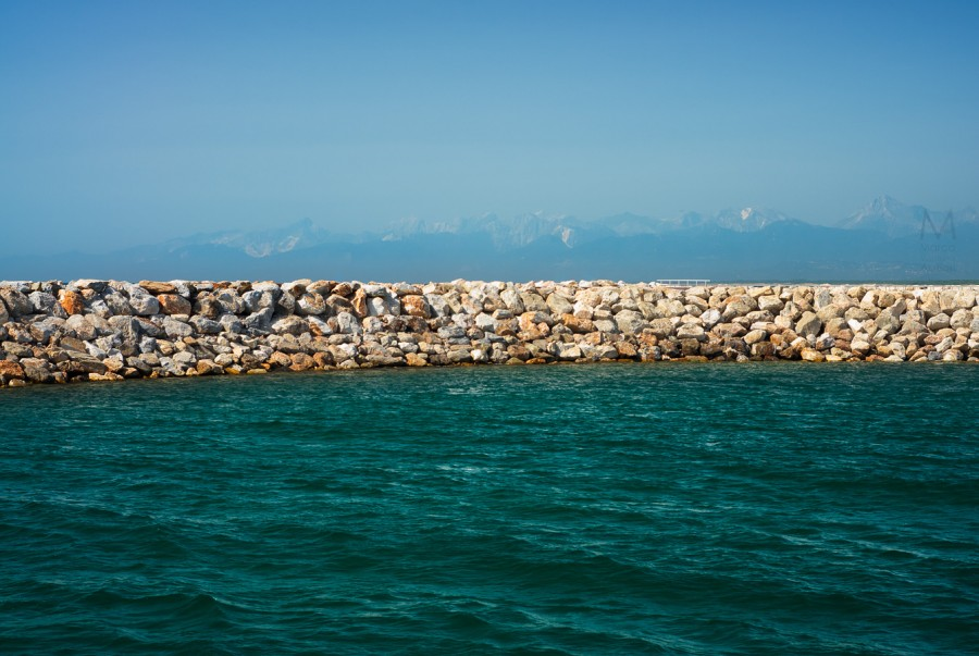 In Marina di Pisa (Pisa) there is a new commercial port, already working, albeit still being erected. Behind this  levee, you can see, distant, the Alps (Alpi Apuane) of Tuscany