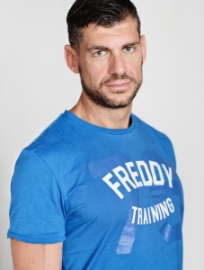 Headshot of confident man wearing FREDDY t-shirt