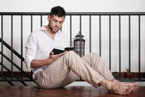 Man sits on the tiled floor, leaning his back onto the staircase's handrail, and reads a novel. Shallow soft focus. CD tower and small furniture in the background