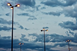 These streetlamps illuminate a car park at dusk. Tuscany, Italy, Summer.