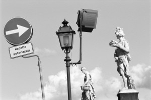 Florence, Italy: the city is so full of artworks that it is impossible to separate it from the normal, modern urban decor necessary for the functioning of the town. Street sign and streetlamp with some statues situated along the River Arno. Scan from Acros 100