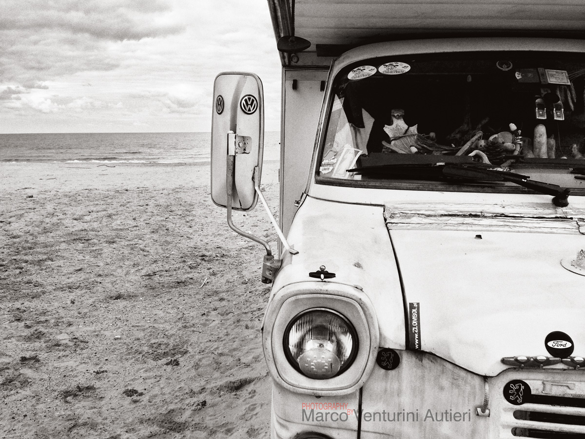 """Alcamo Marina, Italy - December 25, 2014: """"La sicurezza non è un limite"""" (Italian for """"Safety is not a limit"""") is written on one of the many stickers on this eccentric camping van parked on the Sicilian beach on Christmas Day. Many unusual objects are placed on the dashboard of this old Volkswagen camper. Photographed with iPhone 5, toned and digital grain added."""
