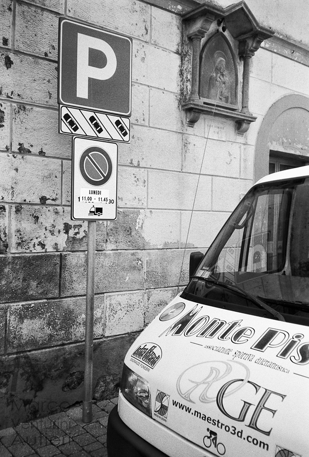 Uliveto Terme, Italy - August 2013: this photo collects several graphical elements of different kinds: one detailed street sign, one Christian icon, a van with several local companies advertised, and an old weathered wall. The scene was photographed in a small village in the municipality of San Giuliano Terme. Uliveto Terme è una frazione di circa 1.300 abitanti posta nel Comune di Vicopisano, in provincia di Pisa. Olympus XA, Eastman Double-X 5222 cine-film. Uliveto Terme (Tuscany, Italy). Graphical elements of the ads printed on the van (perhaps an ambulance) mix with those of the street and the nearby sacred icon and provide a message which is a mixture of sacred and profane, of modern and traditional
