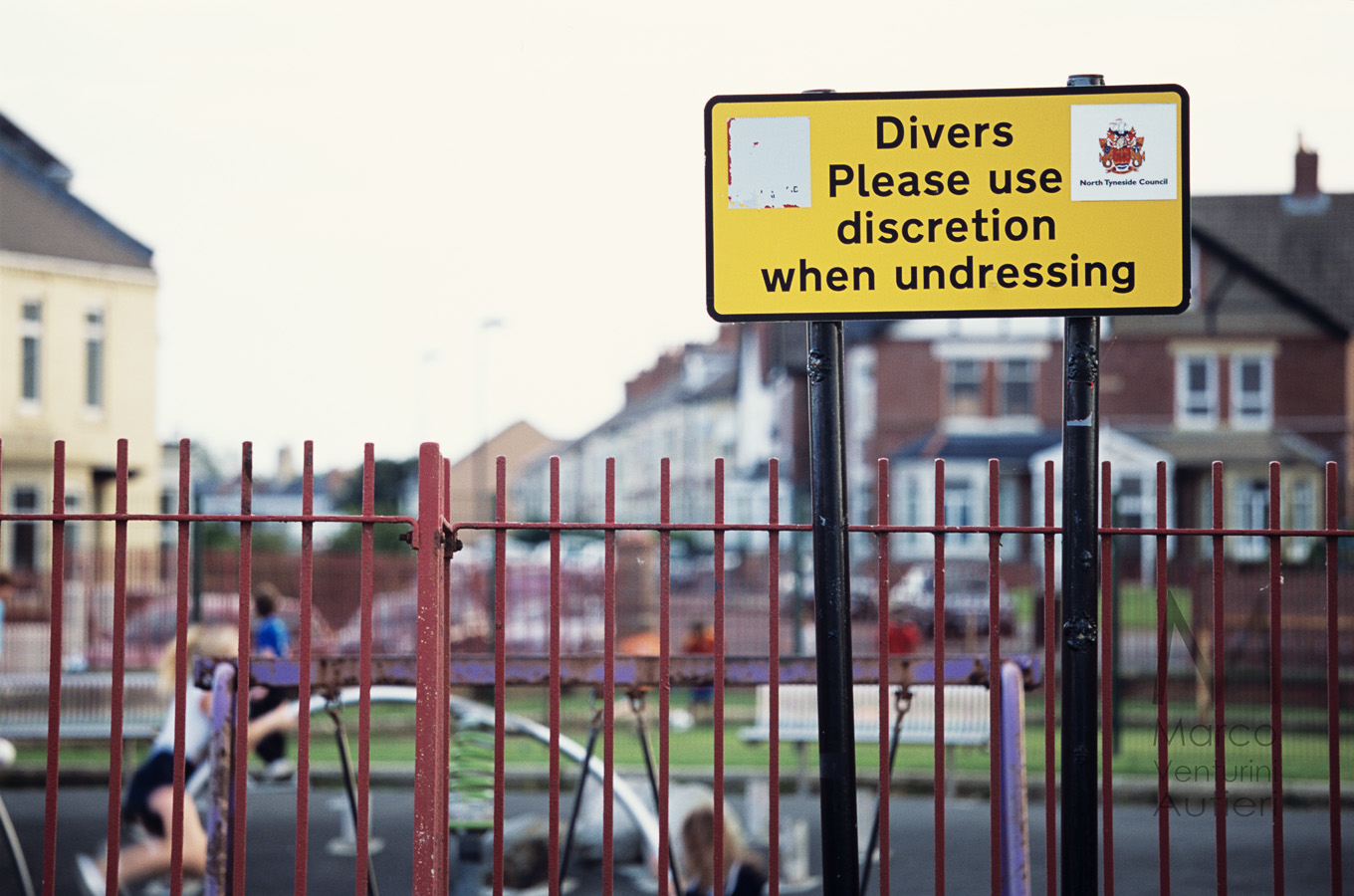 Divers - Please use discretion when undressing! Tynemouth, England - September, 2012: this children's park with swings and other games is situated just on the seafront. A sign from the local council (North Tyneside) invites the divers arriving onshore to mind the public when changing. Canon EOS 1n, EF 70-200 f/4L IS, Provia 100F