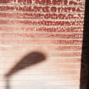 Shadow on a streetlamp (sunny day) on a rusty shop rolling shutter, Italy. iPhone 5