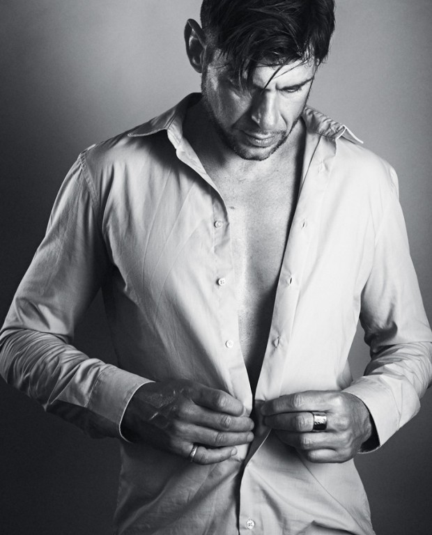 Handsome man unbuttons his shirt - studio shot
